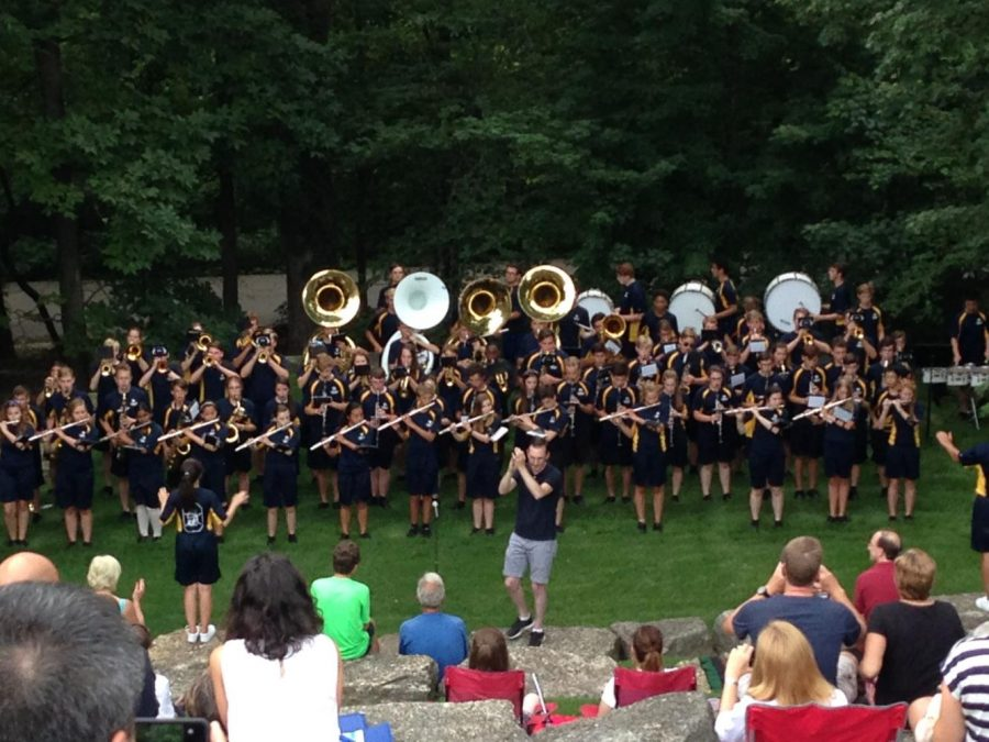 Marching band members play for their families at the band camp picnic.