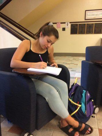 Alison Kordik (12) studies using her phone in the senior hallway.