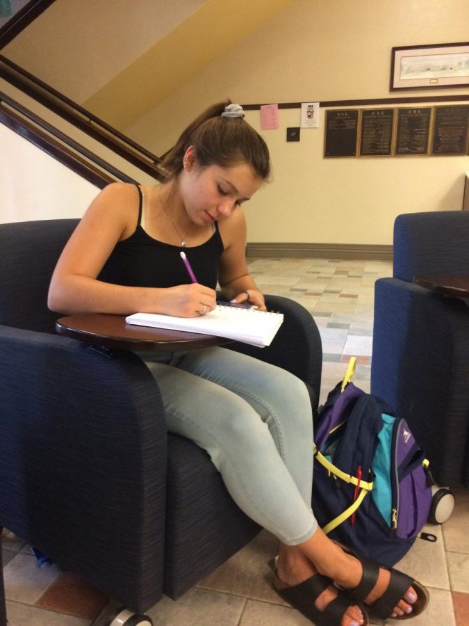 Alison Kordik (12) studies using her phone in the senior hallway.