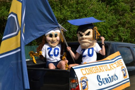 Line leaders: Mascots Lumberjack and Lumberjill, Mrs. Heidi Edwards, cheer coordinator, and Mrs. Kathy Barlow, cheer coach, rode in the bed of a pickup truck and led seniors during the parade. Photo by: The Ax Staff